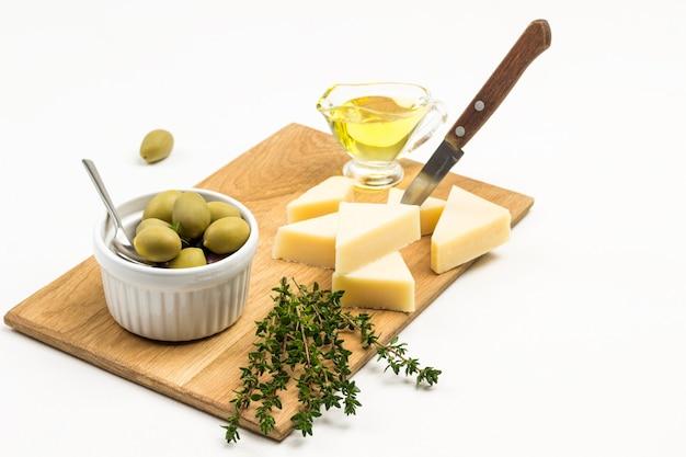 Olijven in ceramische kom. parmezaanse kaas, mes en takjes tijm op snijplank. bovenaanzicht.