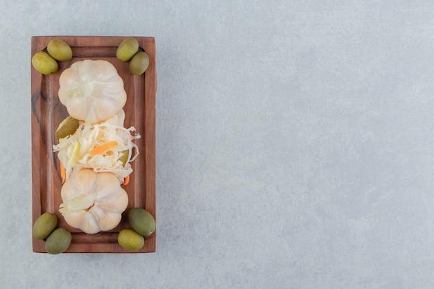 Olijven, knoflook en zuurkoolsalade op de houten plaat op het marmeren oppervlak