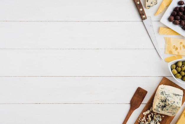 Olijven met emmentaler en blauwe kaasbrok met mes en spatel op wit bureau