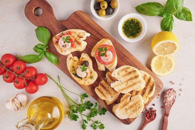 Olijven, olie, gegrilde garnalen en verse groentesalade op een houten bord op zwarte leisteen stenen bord over donkere ondergrond, sappige tomaten op vers brood, pesto als topping. bovenaanzicht. plat leggen