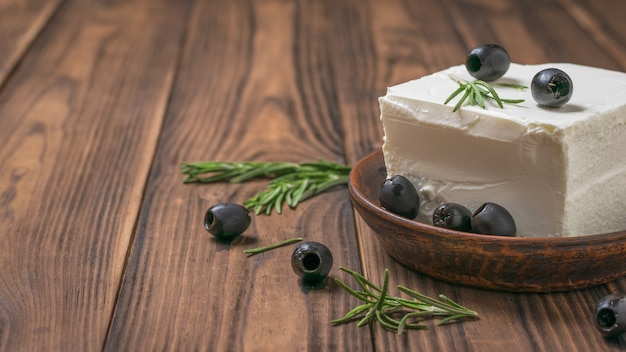 Olijven op een groot stuk fetakaas op een houten tafel. natuurlijke kaas gemaakt van schapenmelk.