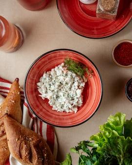 Olivier salade aardappel wortel ei groenen vlees bovenaanzicht