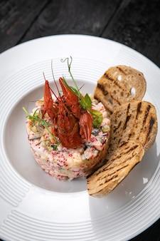 Oliviersalade met zeevruchten en kaviaar op een donkere tafel
