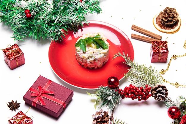 Oliviersalade op een rode plaat. olivier kerstmis. kerstlay-out met salade. nieuwjaar. vakantie. feestelijk gerecht. tafeldecoratie. de hoofdsalade. het uitzicht vanaf de top