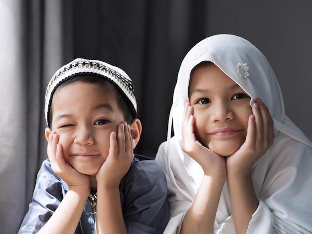 Olympus digital cameraaclose-up shot van aziatische moslimkinderen. jonge zus en broer broer of zus in traditionele islamitische kleding. gelukkig en op zoek naar camera. concept van gelukkig kind in ramadan of familieband.