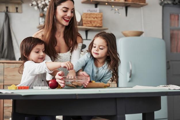Om deze heerlijke dingen te bereiken. de jonge mooie vrouw geeft de koekjes terwijl zij dichtbij de lijst met speelgoed zitten