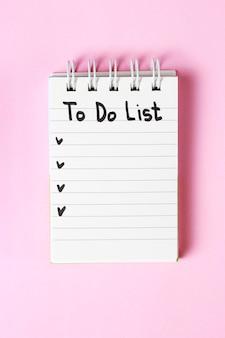 Om lijst in notitieboekje op roze achtergrond, exemplaarruimte, planningsconcept te doen