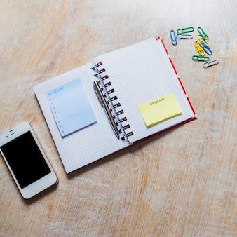 Om lijstblocnote en dringende kleverige nota op geruite laptop met smartphone en paperclip te doen