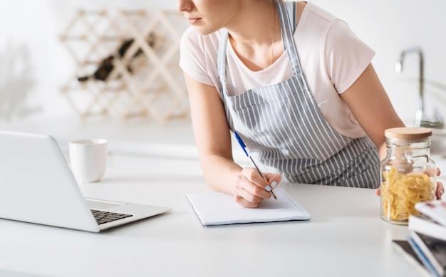 Om niets te missen. gerichte, gracieuze jonge vrouw die het pastarecept opschrijft dat ze online opzoekt terwijl ze een van de ingrediënten in haar hand houdt