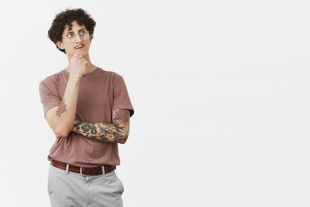 Om te zijn of niet, dat is de vraag. nadenkende artistieke en creatieve slimme man met krullend haar in bril met snor en coole tatoeages op armen, kin wrijven omhoog staren terwijl hij denkt een plan in gedachten te houden