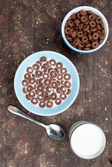 Om verre mening te bekijken chocolade granen met melk in blauwe plaat en samen met lepel op bruin, granen ontbijt eten gezondheid