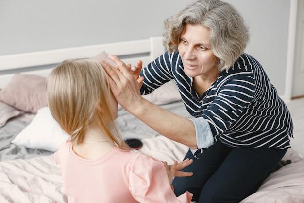 Oma brengt tijd door met haar kleindochter in de slaapkamer
