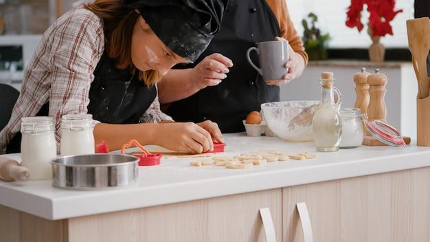 Oma die laat zien hoe je de vorm van koekjes aan kleinkind kunt gebruiken