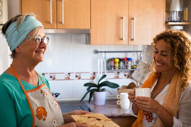 Oma en dochter koken thuis en glimlachen - genieten en hebben samen plezier binnenshuis - dochter drinkt de en oma laat zien hoe je vis kookt
