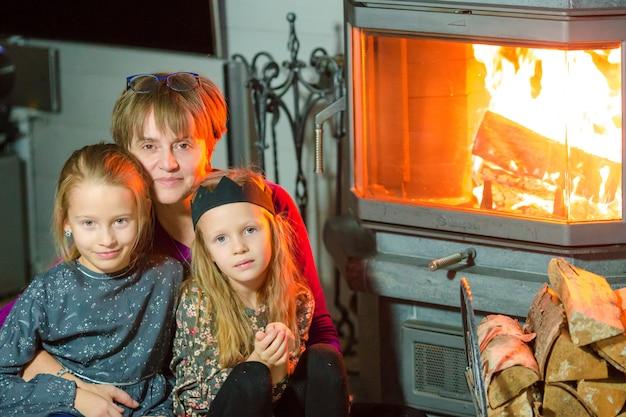 Oma en haar twee kleine kleindochters zitten bij een open haard in hun ouderlijk huis op kerstavond