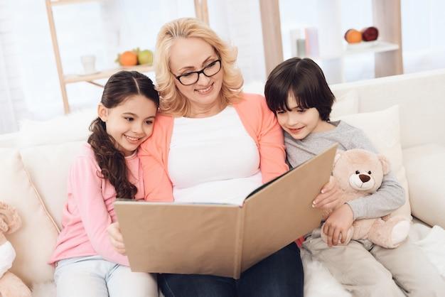 Oma en kinderen samen op zoek fotoalbum