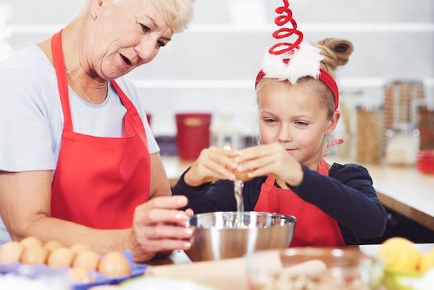 Oma en kleindochter bereiden snack in keuken