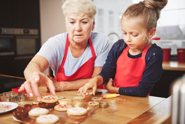 Oma en kleindochter die koekjes versieren