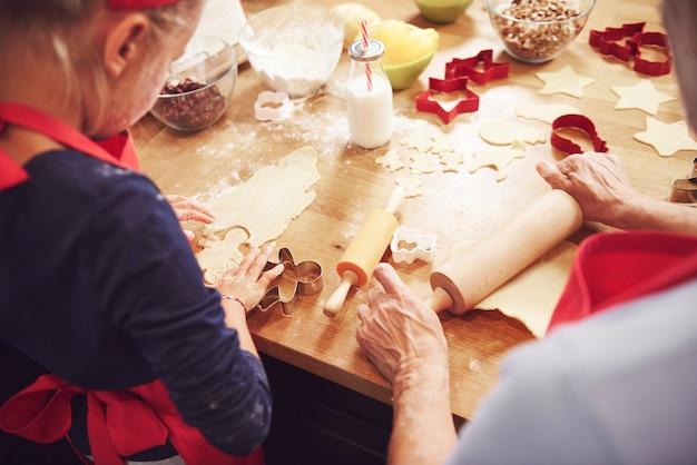 Oma en kleindochter die koekjes voorbereiden
