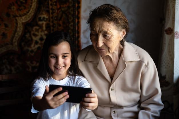 Oma en kleindochter. een schattig klein meisje laat haar grootmoeder een smartphone zien.