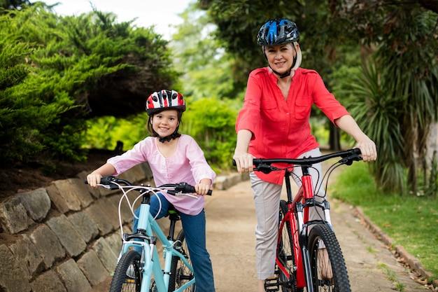 Oma en kleindochter fietsen in het park
