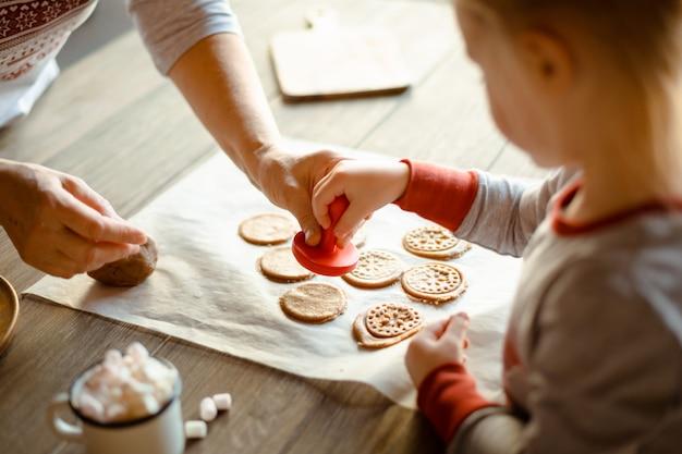 Oma en kleindochter in de ochtend in dezelfde pyjama bakken samen kerstkoekjes-stempels op de test. het gezellige concept van kerstmis.