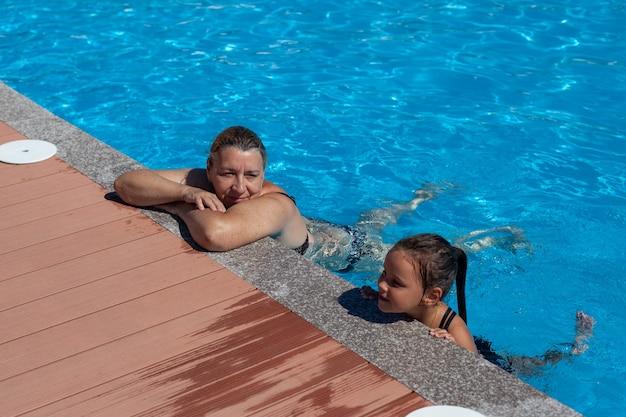 Oma en kleindochter in het zwembad een jonge grootmoeder en kleindochter ontspannen met hun hand...