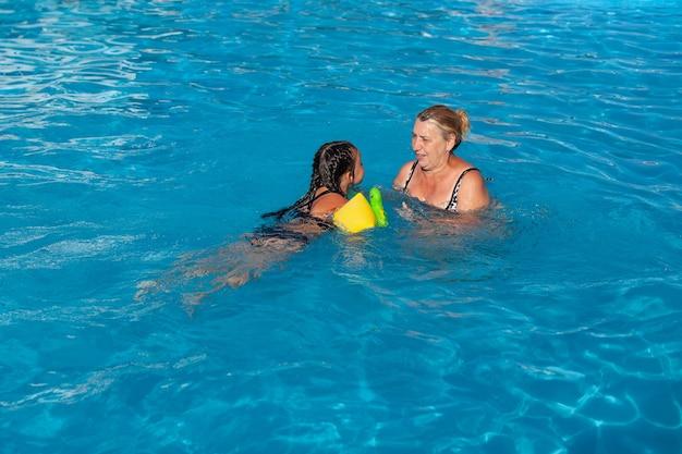 Oma en kleindochter in het zwembad een vriendelijke oma leert haar kleindochter zwemmen in gr...