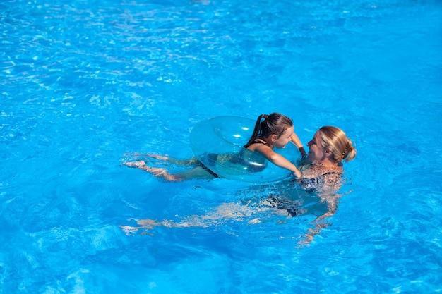 Oma en kleindochter in het zwembad oma en kleindochter spelen inhaalslag in het heldere z...