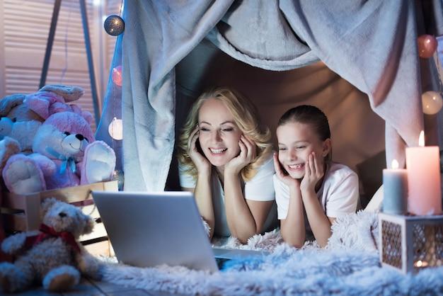 Oma en kleindochter kijken film op laptop.