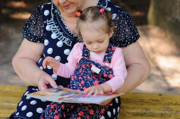 Oma en kleindochter lezen het boek in het park