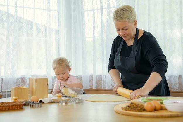 Oma en kleindochter rollen deeg op houten tafel bestrooid met bloem. familietradities concept. saamhorigheid concept. zelfgemaakte bakles concept. bloggen concept