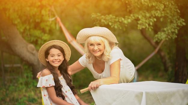 Oma en kleindochter zitten aan tafel in de tuin