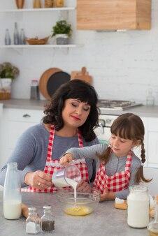 Oma en kleine kleindochter met staartjes in koksschorten samen koken in de keuken