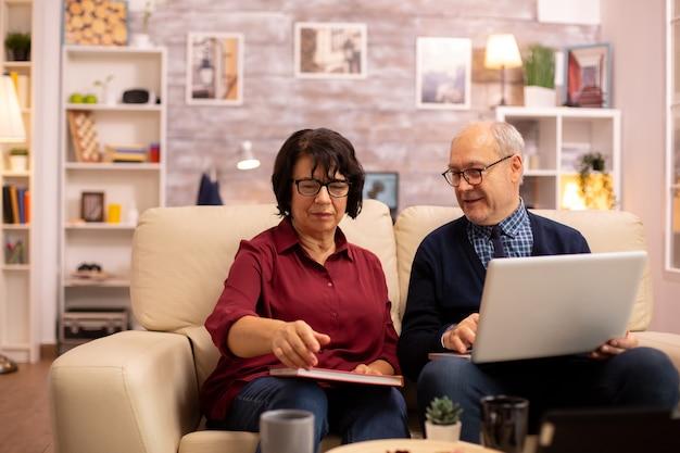 Oma en opa gebruiken een laptop om met hun kleinzonen te chatten. oude mensen die moderne technologie gebruiken