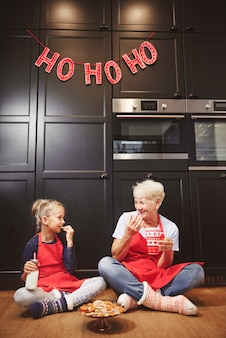 Oma en schattig meisje eten zelfgemaakte koekjes