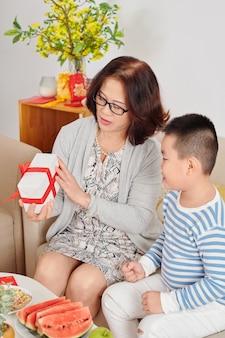 Oma geeft cadeau voor nieuw maanjaar aan haar kleinzoon wanneer ze op de bank in de woonkamer zitten