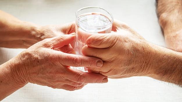Oma geeft opa een glas water. selectieve aandacht. voedsel.