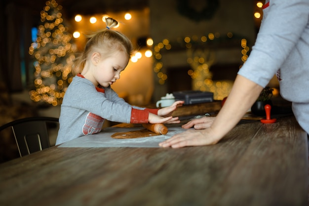 Oma helpt haar kleine kleindochter het deeg uitrollen voor een traditioneel kerstkoekje met gember