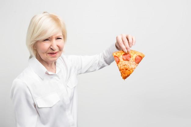 Oma houdt niet van het idee om dit stuk pizza te eten, omdat het niet goed en gezond is voor de mens.