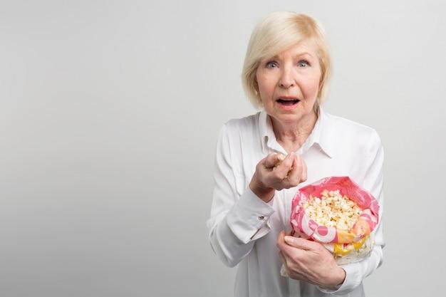 Oma kijkt graag naar tekenfilms, films en verschillende tv-series - dat doen jonge mensen graag. deze vrouw ziet eruit als een zeer moderne oude vrouw.