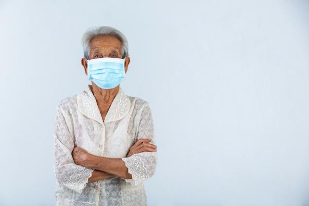 Oma knuffelt zichzelf en geniet van haar leven op de witte muur. - concept maskercampagne.