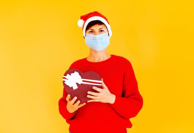 Oma met een kabouterpet en een medisch masker heeft een nieuwjaarscadeau. op een zwarte fotostudio als achtergrond. gelukkig nieuwjaar 2021.