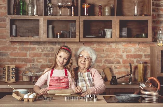 Oma met kleindochter rol het deeg uit