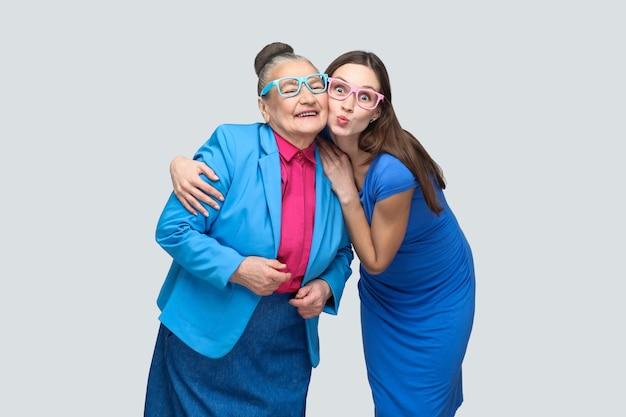 Oma met kleinkind knuffelen en veel plezier samen in het gezin. kus en brede glimlach en goede relatie. vriendschap en wederzijds begrip. binnen, studio-opname, geïsoleerd op een grijze achtergrond