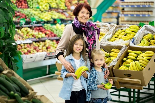 Oma met kleinkinderen kiest groenten en fruit in een grote supermarkt.