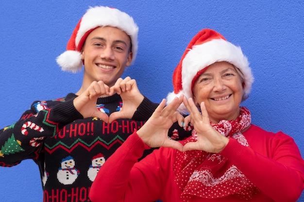 Oma met lachende kleinzoon die een hartvorm maakt met een kersttrui en een kerstmuts