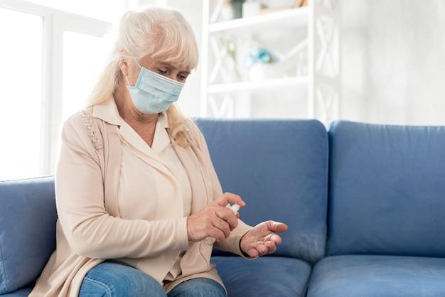 Oma met masker met ontsmettingsmiddel