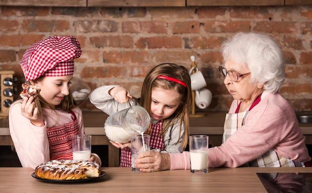 Oma met twee kleine kleindochters zitten aan tafel in de keuken