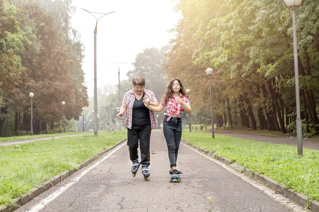 Oma op rolschaatsen en een kleindochter op een skateboardrit in het park